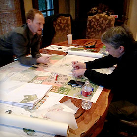 Photo of two men working at table over floor plans