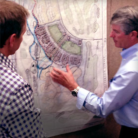 Photo of two men discussing site plans
